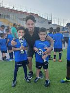 פליקס חלפון מחבק שני ילדים מבית הספר לכדורגל שאוחזים בגביע שקיבלו