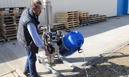 פועל מדגים שפיכת נוזל מחבית באמצעות כלי הרמה חשמלי
