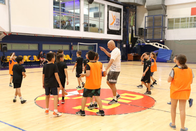 ילדים המשחקים כדוריד עומדים סביב מאמנם