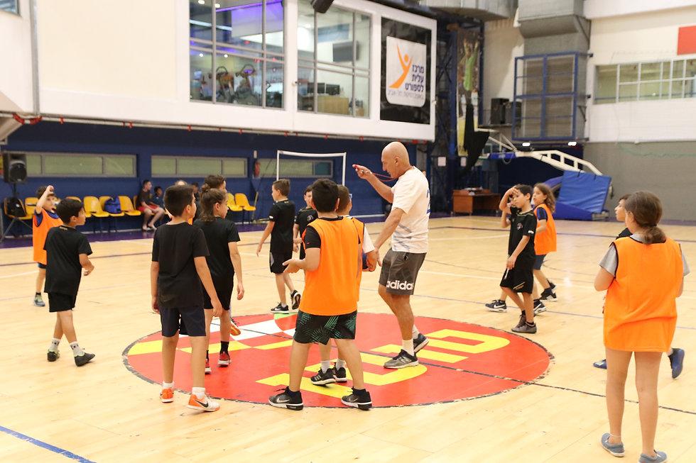 מאמן בית הספר לכדוריד במהלך תדרוך מקצוע לשחקנים