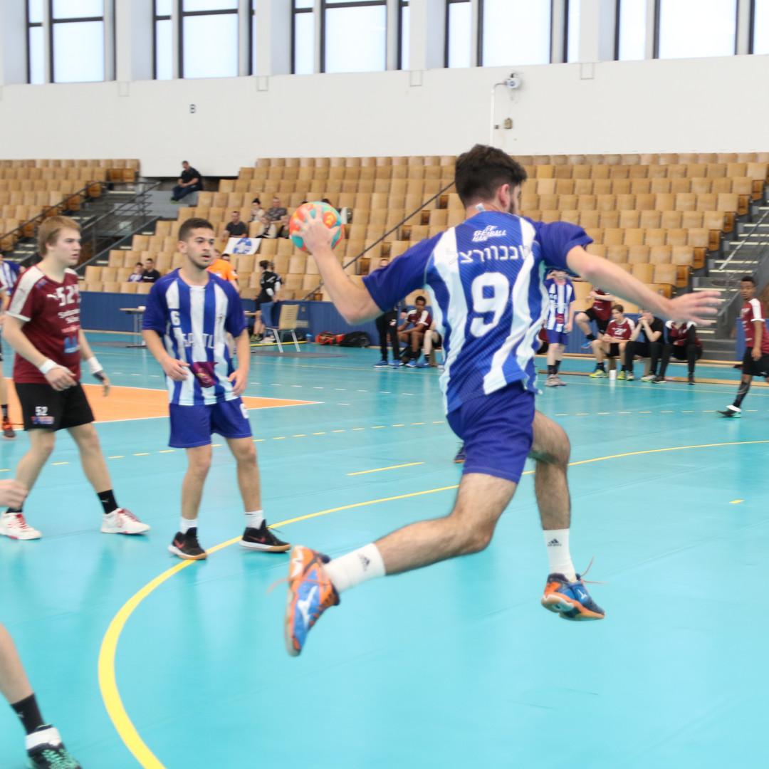שחקן נוער אסא תל אביב מנתר תוך כדי זריקת כדור לשער ששחקנים אחרים מביטים לעברו