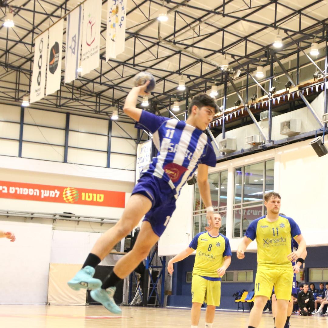 שחקן נוער אסא תל אביב במהלך קפיצה וזריקת כדור לשער ששחקני הקבוצה היריבה מביטים בו