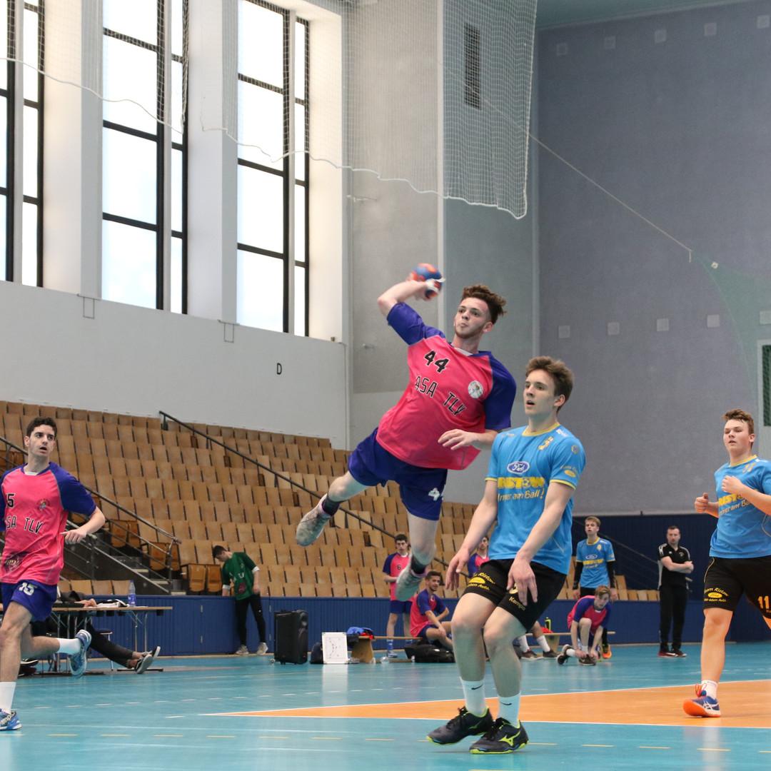 שחקן נוער אסא תל אביב מנתר מעל שחקן יריב תוך כדי זריקת כדור לכיוון השערשער