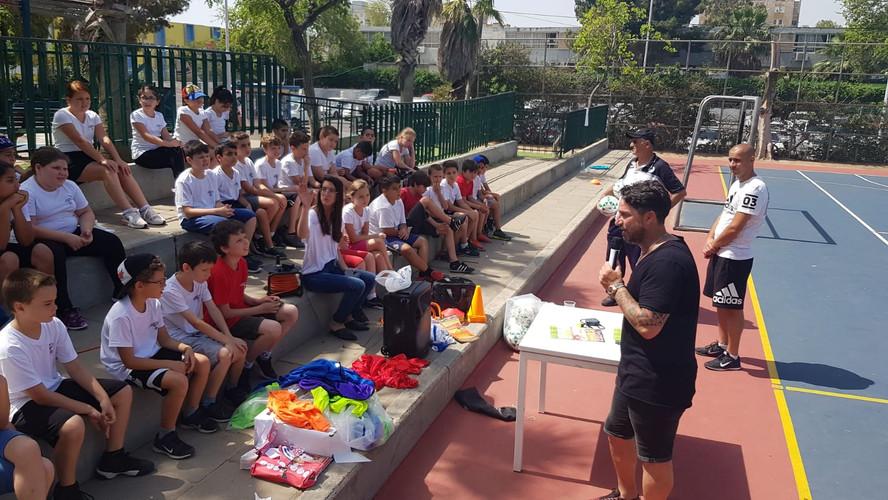 פליקס חלפון שלצידו צוות מאמן משוחח עם תלמידים שיושבים מולו, לקראת אימון כדורגל