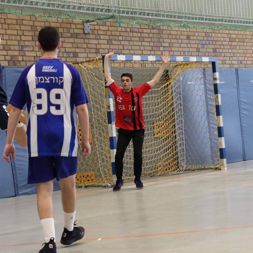 שחקן יריב מנסה להבקיע שער לשוער נוער אסא תל אביב כששחקן נוסף מביט בו