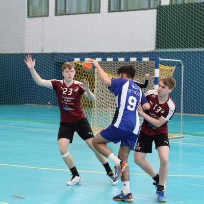 שחקן אסא תל אביב עומד על רגל אחת וכדור בידו ומנסה לעבור בין שני שחקני הגנה