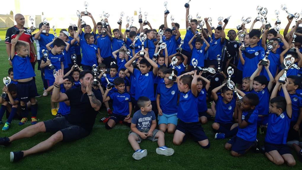 סיום שנה בית הספר לכדורגל 2019, פליקס חלפון וילדי בית הספר מניפים גביעי הוקרה שקיבלו.jpeg