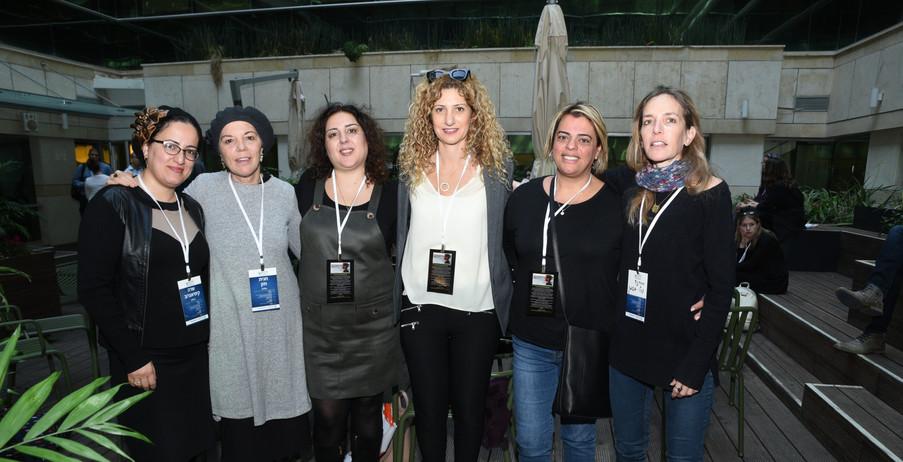 שש נשים עומדות מחובקות אחת ליד השנייה