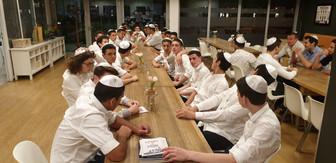 """שחקני מחלקת הנוער של אס""""א תל-אביב יושבים ליד שולחן ליל הסדר"""