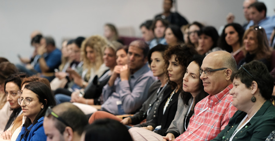 קהל יושב באולם ומאזין להרצאה