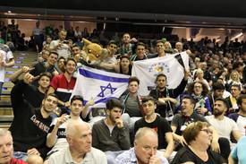 """שחקני נוער אס""""א תל-אביב עם דגל ישראל צופים במשחק כדוריד מהליגה הגרמנית פוקסה נגד קיל"""