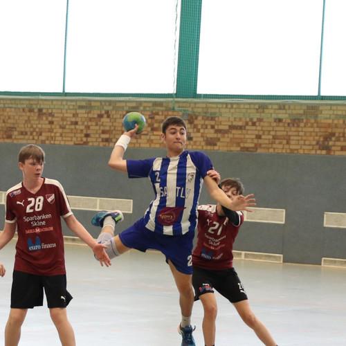 שחקן נוער אסא תל אביב משתחל בין שני שחקני הקבוצה היריבה ומנתר לפני זריקת הכדור לשער