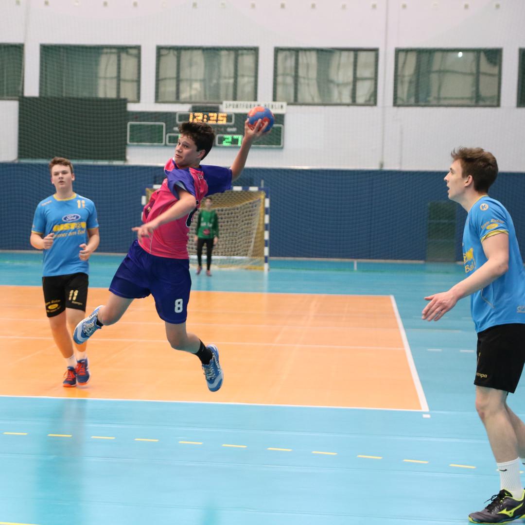 שחקן נוער אסא תל אביב מנתר עם שתי רגליו ומנסה לזרוק לכיוון השער שסביבו שלושה שחקני קבוצה יריבה
