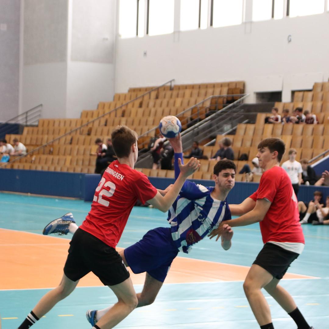 שחקן נוער אסא תל אביב קופץ בין שני שחקני קבוצה יריבה לפני זריקת הכדור לשער