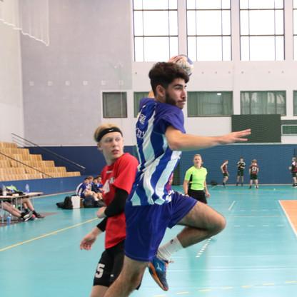 שחקן נוער אסא תל אביב קופץ לפני זרקת כדור שמאחוריו שחקן יריב מביט בו