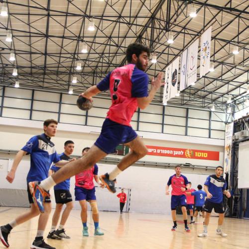 שחקן נוער אסא תל אביב קופץ וזורק את הכדור ששחקני הקבוצה היריבה מביטים בו