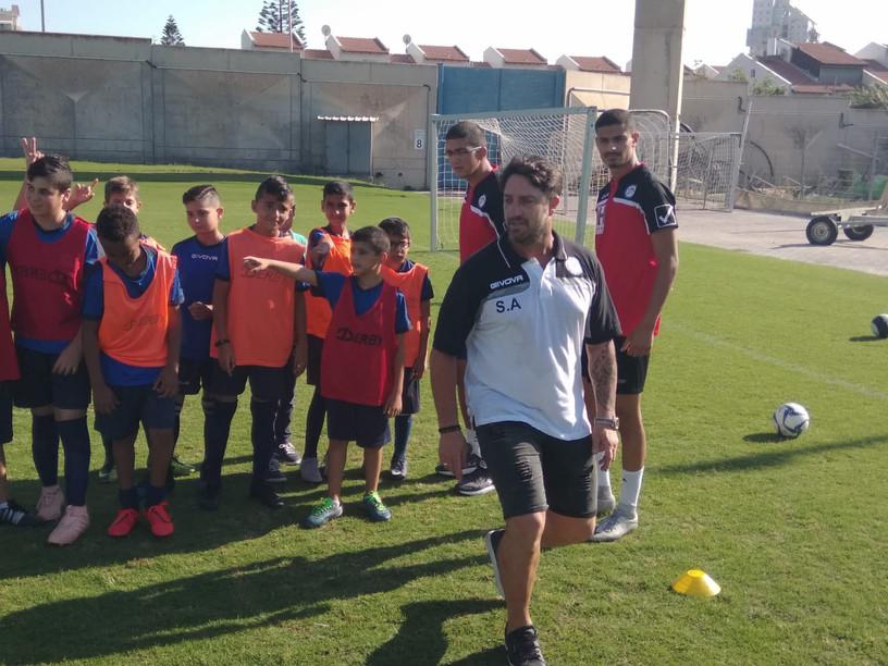 פליקס חלפון מדגים ומתדרך את ילדי בית הספר לכדורגל במהלך אימון