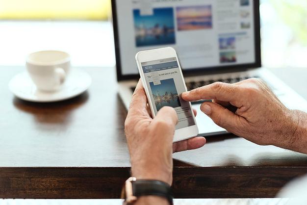 יד מדפדפת בטלפון חכם וברקע מחשב נייד