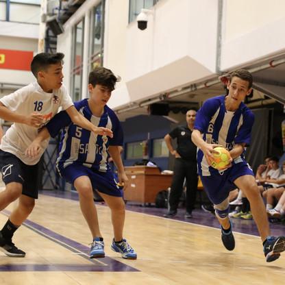 שחקן נוער אסא תל-אביב בריצה עם כדור שחברו לקבוצה חוסם שחקן יריב