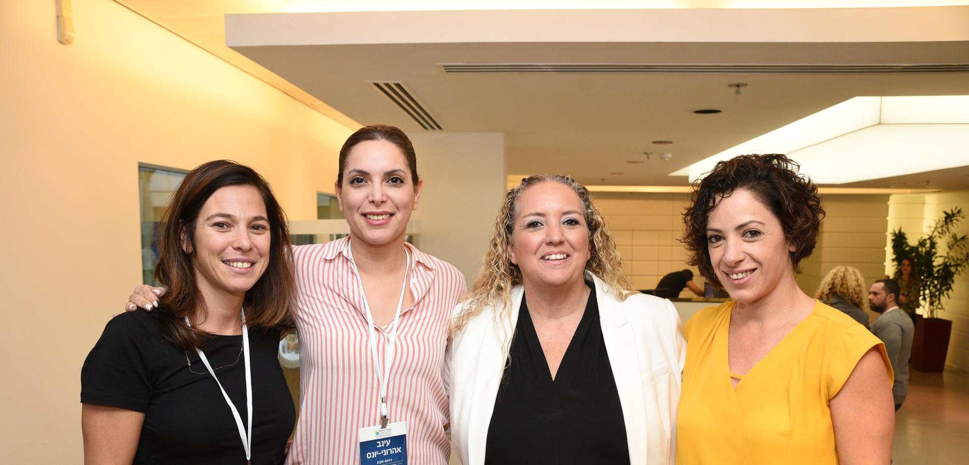 ארבע נשים עומדות מחובקות אחת ליד השנייה