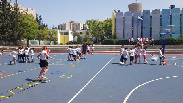 תלמידי בית הספר בתרגילי כדורגל במהלך הפסקה פעילה