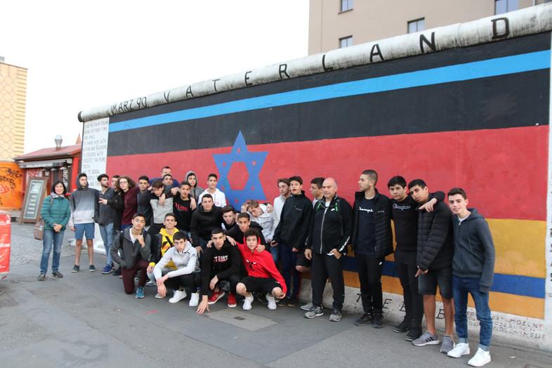 שחקני מחלקת הנוער עומדים לפני חומת ברלין עליה מצויר דגל גרמניה וישראל