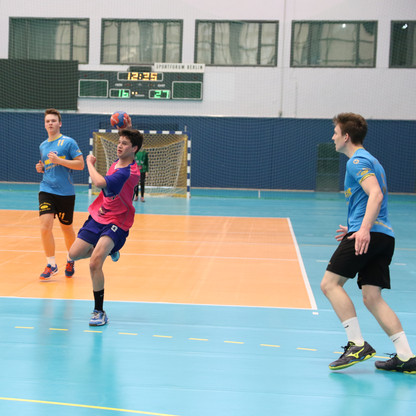 שחקן נוער אסא תל אביב עומד על רגל אחת עם כדור בידו שהוא בין שלושה שחקני קבוצה יריבה