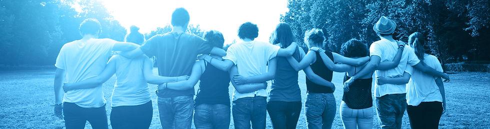 קבוצת צעירים בגבם מתחבקים