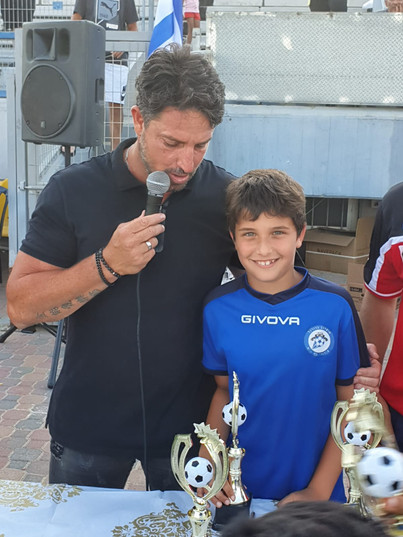 פליקס חלפון מדבר במיקרופון להורי בית הספר לכדורגל שלידו אחד הכדורלגנים