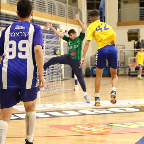 שוער נוער אסא תל אביב מנסה לעצור כדור של שחקן יריב שלובש חולצה צהובה