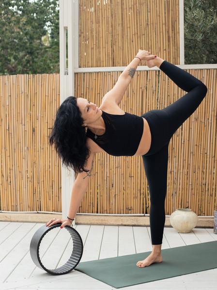 רנטה לוקאש מדגימה תנוחות יוגה עם גלגל דר