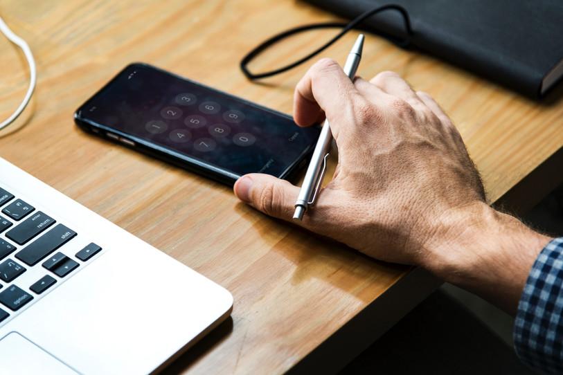 יד אוחזת בסמארטפון שמונח על שולחן עבודה