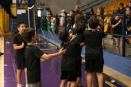 קבוצת בנים עומדת באולפ ספורט בסמוך ליציע