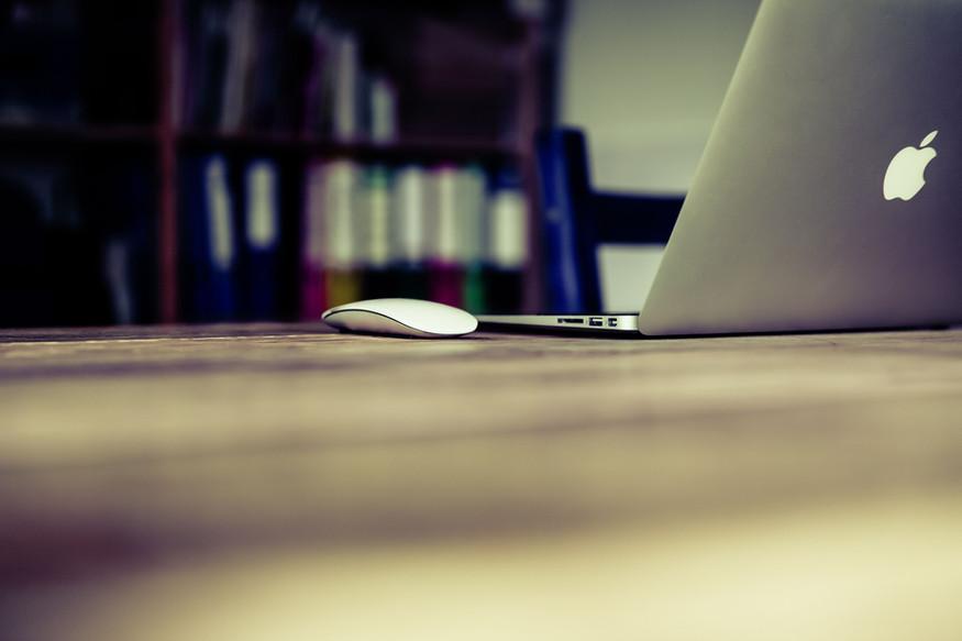 מחשב נייד ועכבר מונחים על שולחן עבודה.jp