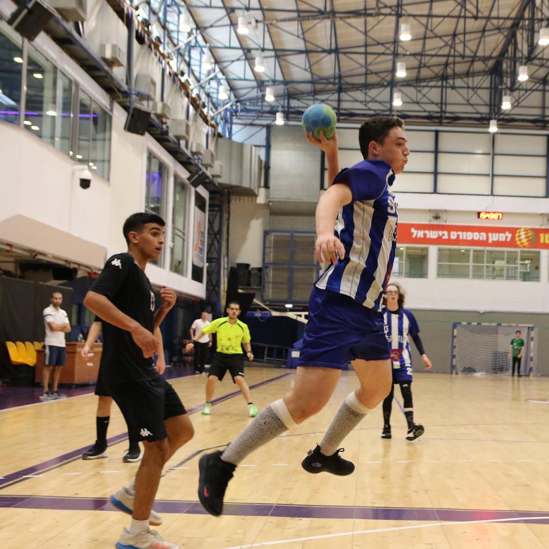 שחקן נוער אסא תל אביב לפני זריקת כדור לשער ששחקני הקבוצה היריבה מביטים בו