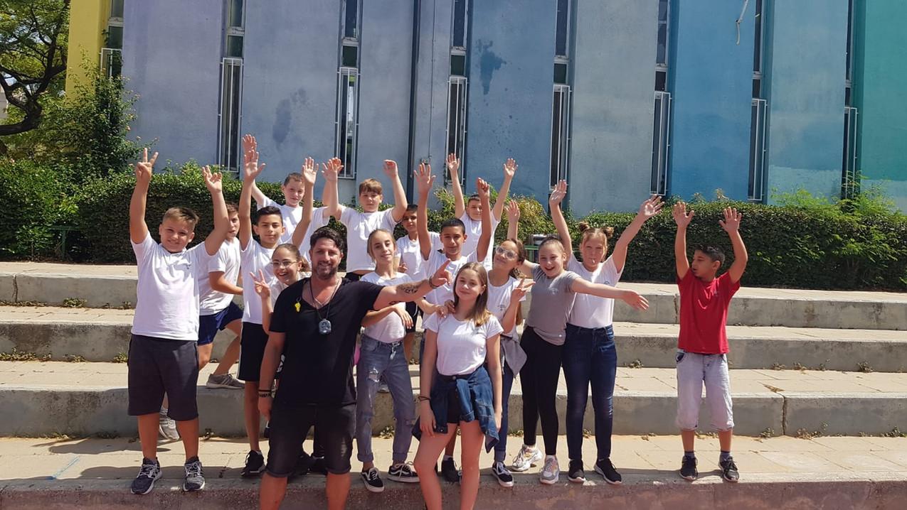 פליקס חלפון ותלמידים מנופפים לשלום