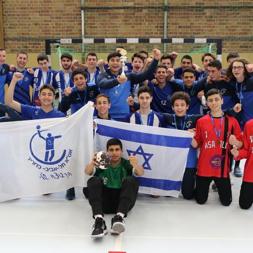 תמונה קבוצתית עם דגלי ישראל ואסא יחד עם גביע בו זכו בטורניר ברלין