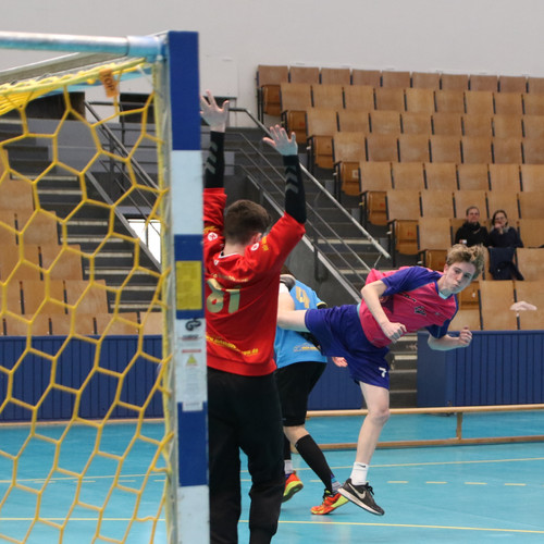 מבט מאחורי השער כשחקן נוער אסא תל אביב מנתר מעל שחקן יריב שהשוער מנסה להגן