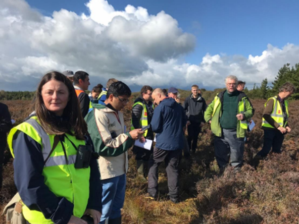 A group of people standing on a peatland area