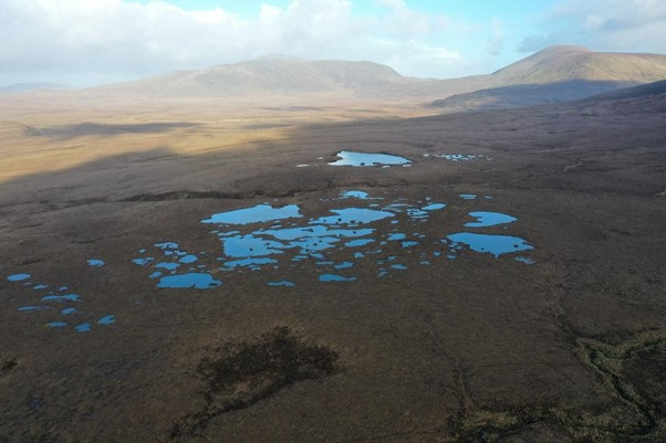 Small blue lakes set in brown bog with hills & sky in background