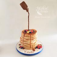 Gravity defying pancake cake with syrup.
