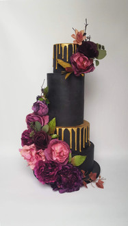 Black and gold wedding cake with purple floral