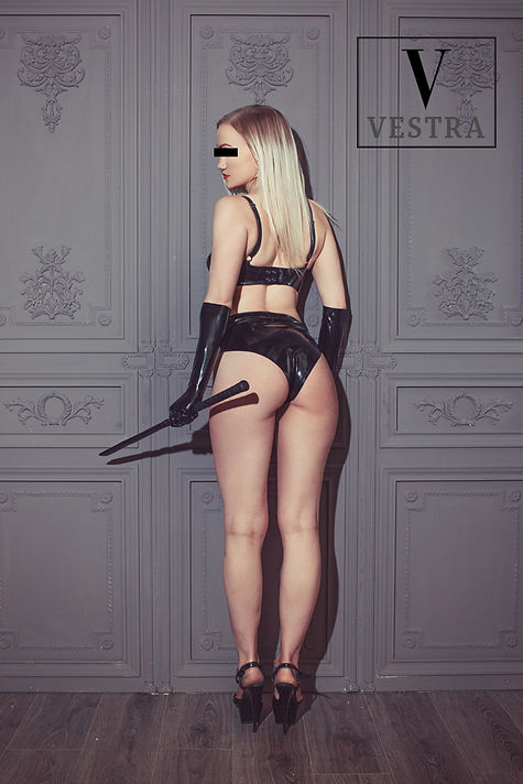 Dominatrix Vestra Sin in high heels latex booty shorts and latex gloves with a riding crop