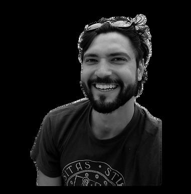 Imagem em escala de cinza do apresentador do Literatura Viral, Áureo Lustosa Guérios. Áureo aparece sorrindo e olhando para a câmera, com barba, cabelos despenteados e óculos na cabeça. Ele usa uma camiseta da Universidade de Pádua. Sorri amplamente.