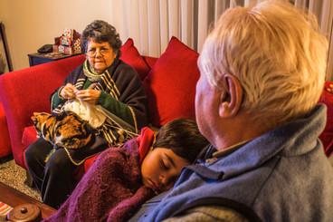 Abuelos mirando tele y cuidando a su nieto