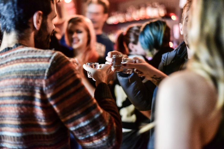 friends-cheers-with-shot-glasses-in-bar.
