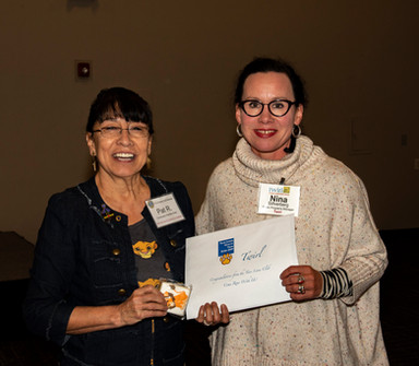 Nina Silfverberg, Public Programs Manager with Twirl accepts a grant from Pat Rutherford, Community Charities Director, at the Annual Taos Lions Gives to Taos Kids Luncheon.