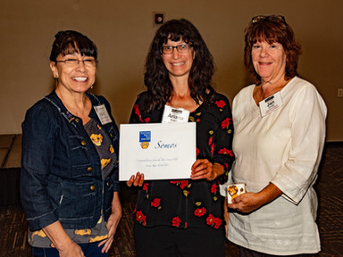 Pat Rutherford, Community Charities Director of the Lions Club of Taos, presents Ariana Kramer & Jan Smith of Somos their grant for the work they do with Young Writers in Taos.