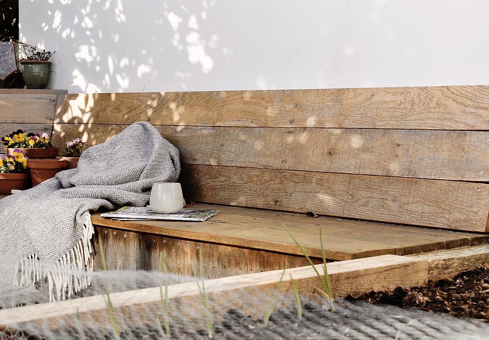 oak garden bench with grey woollen blanket and coffee mug, with dappled morning sunlight