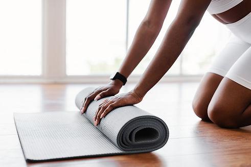 young-black-woman-unrolling-yoga-mat-on-floor-9GKF8HA.jpg